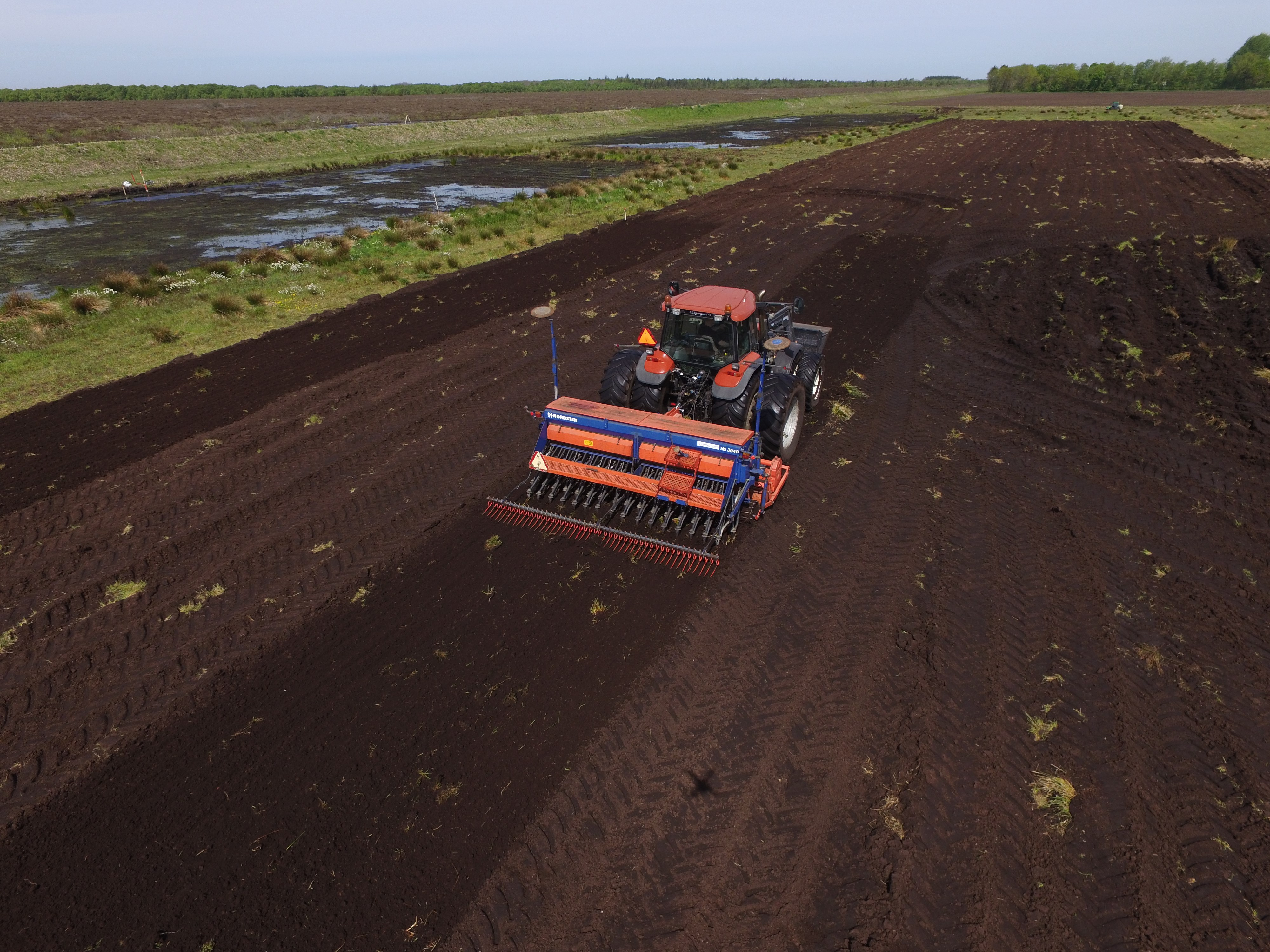 Machinery working to prepare the peat surface.
