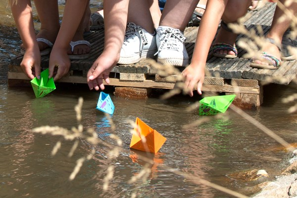 Children playing with paper boats in a lake